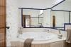 La zona de relax está decorada con espejos y paredes de piedra ibicenca y acoge a una bañera grande de hidromasaje